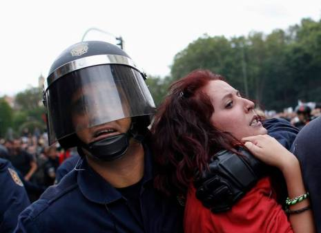 Protester grimaces as she is dragged away by riot police outside Spanish parliament in Madrid